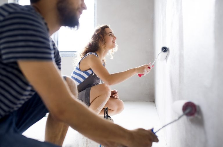 Young couple painting walls in their new house after having equity
