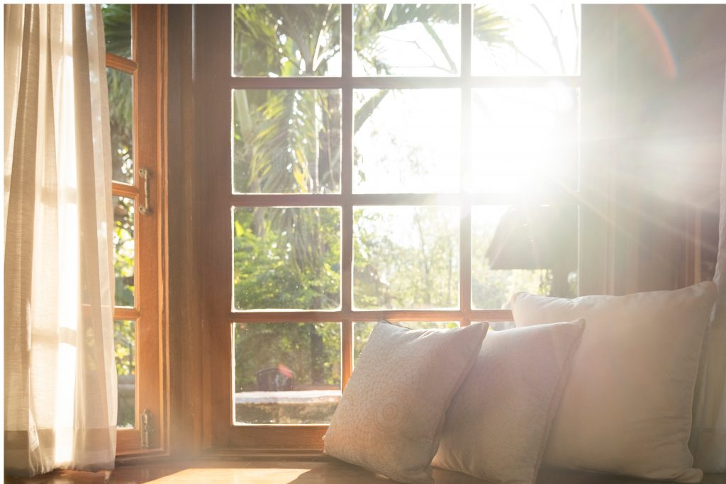 interior view of a cosy living room, sun shining through the window.
