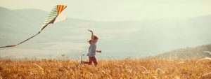 Young girl running with a kite through field. Hazy mountains and fields in the background