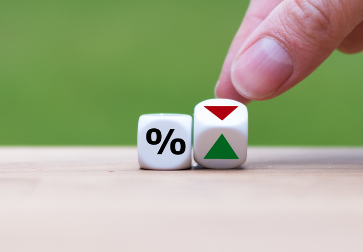 Two financial dice with a percentage symbol and green and red
