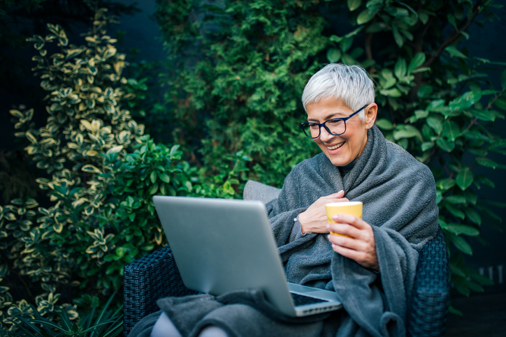 A mature lady sitting on a bench wrapped in a blanket looking at her pension age
