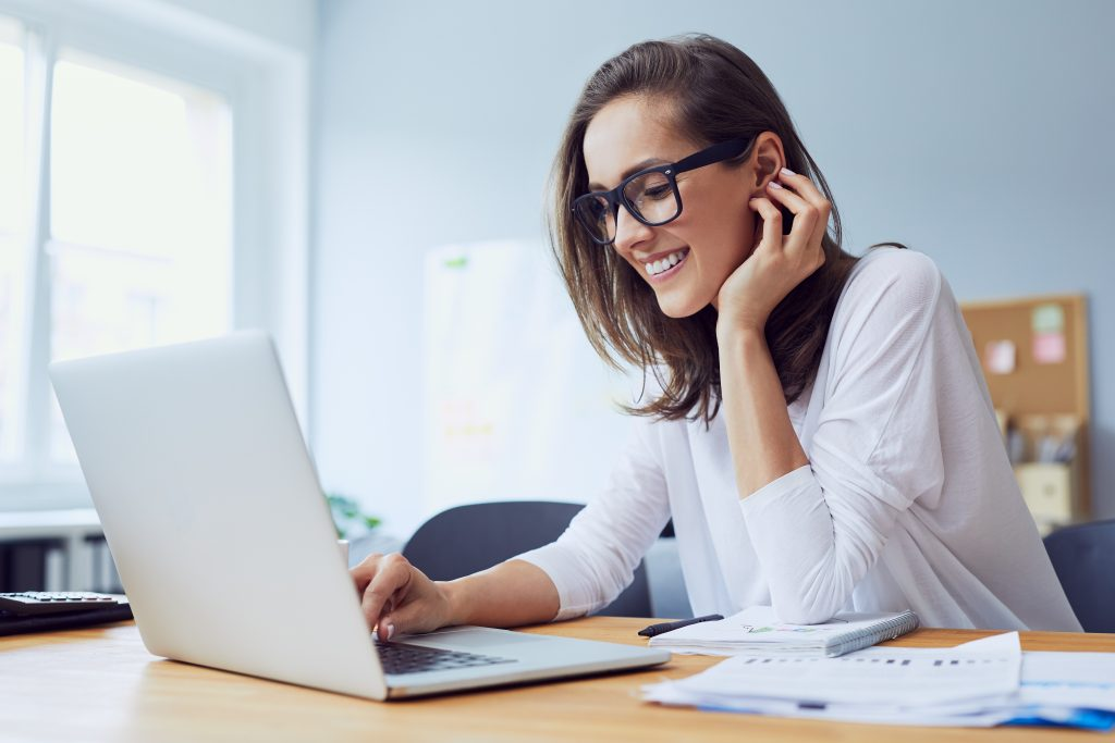 A young woman with glasses sitting at desk smiling working on her laptop