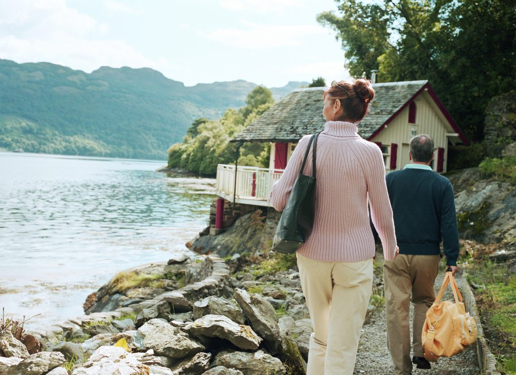 a couple walking along a coast path to their holiday home