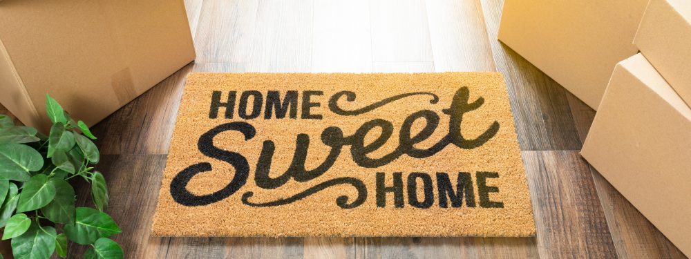 Front door mat with 'home sweet home' written on it, on a wooden floor and boxes around it