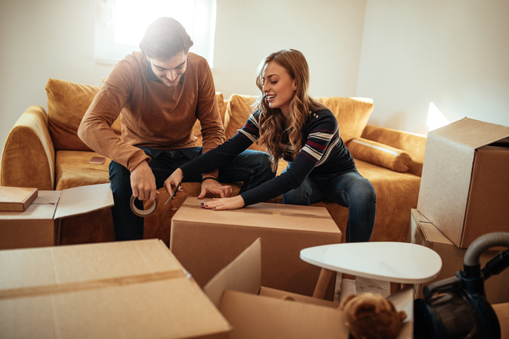 A young couple packing boxes, happy with their mortgage