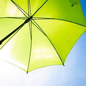 Green umbrella in sunny day with blue sky background