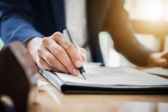 A pen in someone's hand as they sign papers, sorting out the mortgage during their divorce