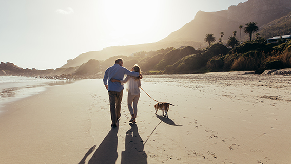 A couple walk on beach with their dog, happily planning to retire in 2021