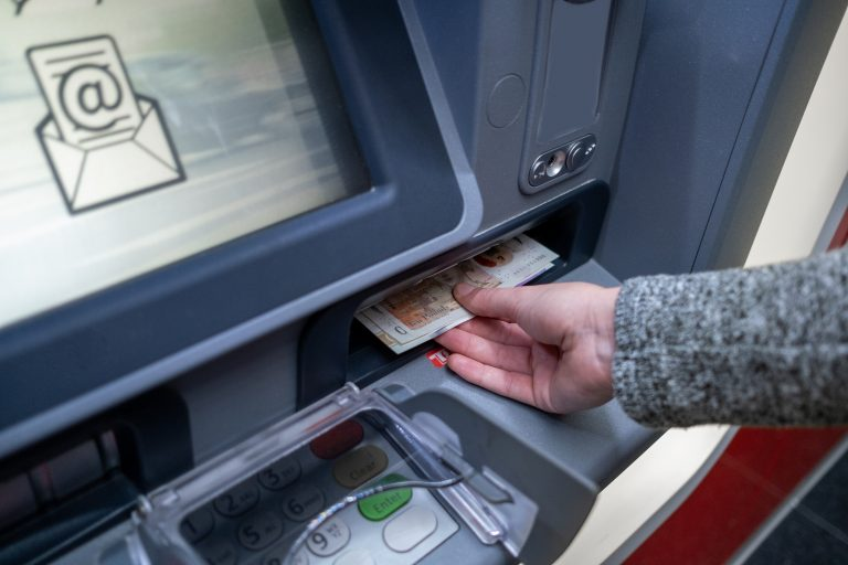 Person at cashpoint withdrawing pension cash