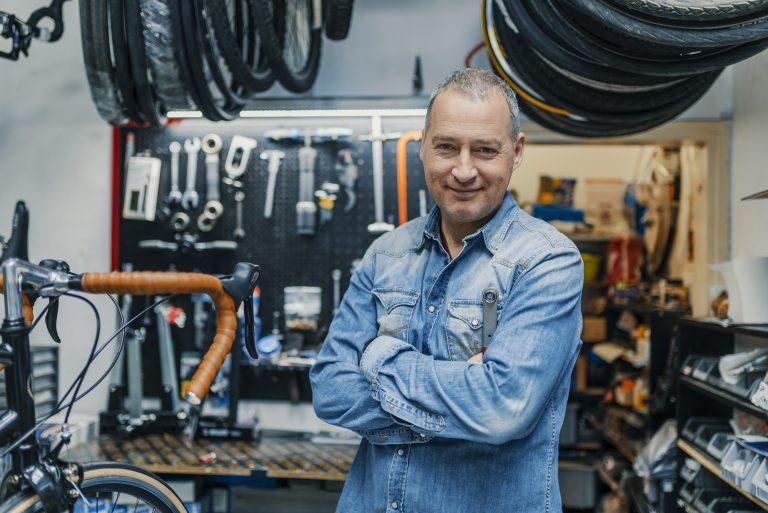 Man repairing bikes in his garage as a side hustle