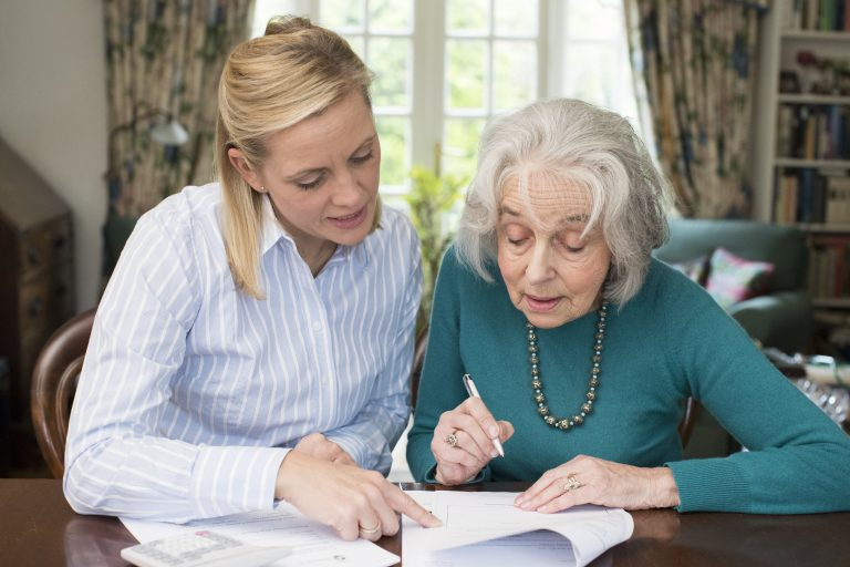 Adviser helping elderly lady at home with paperwork and taking control of her retirement finances