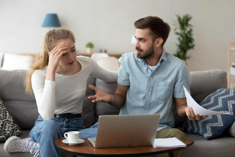 Stressed young couple looking at how to divide up finances on laptop