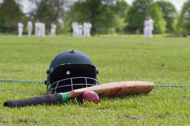 Cricket equipment with a match in background, a summer of sporting events