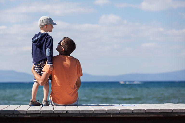 Father and son on holiday being photographed, away from home