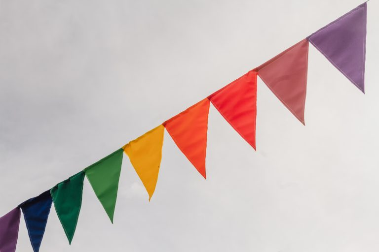 Red flag among colour pennants against clouds in the sky with sunshine