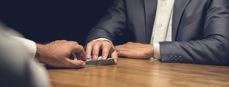 Businessman secretly handing over cash, secret account