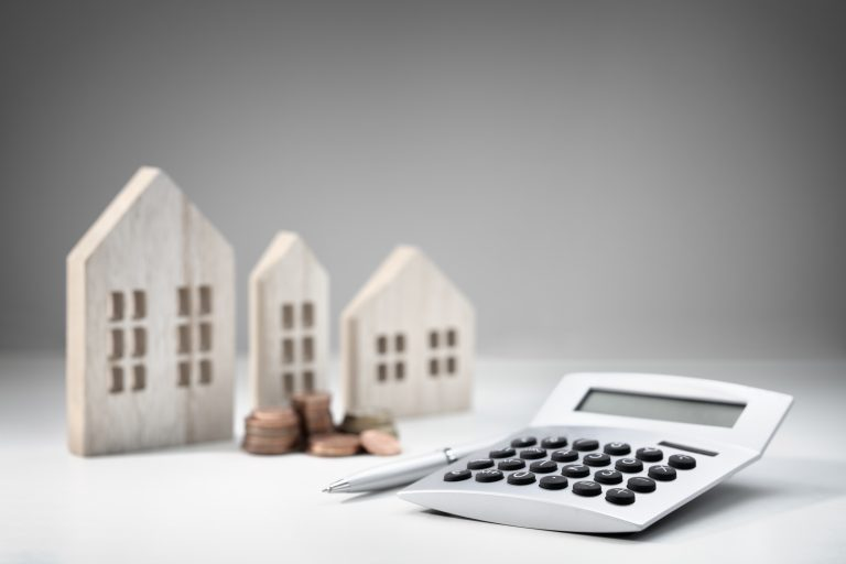 Model houses with calculator and piles of coins, counting up your home's value