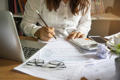 Lady with pencil on paper at desk with laptop and calculator in foreground, getting organised for the Autumn