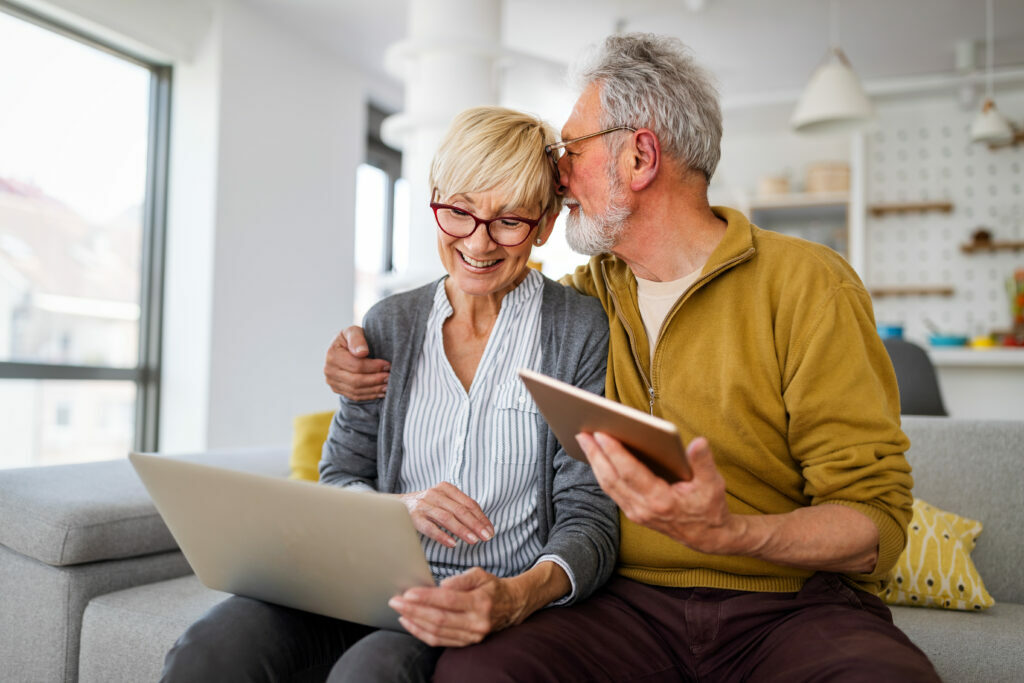 Retired couple at home on laptop, checking pension rates and IHT receipts